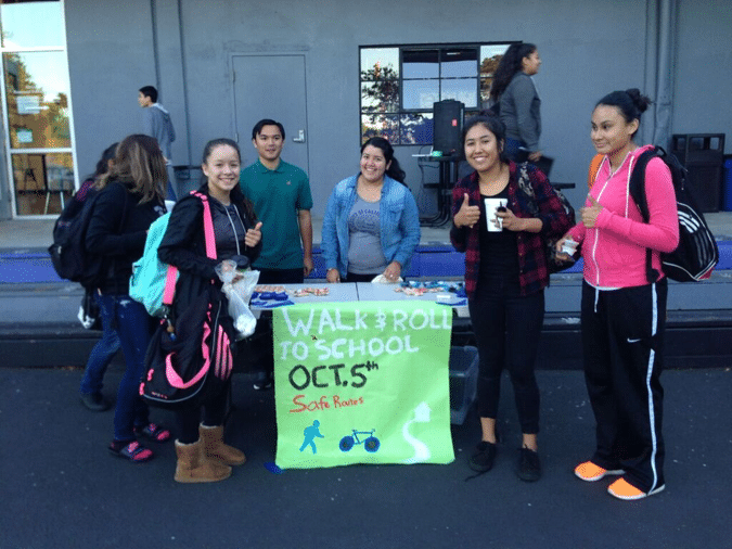 RUP student leaders greeting walkers with a cup of hot chocolate.