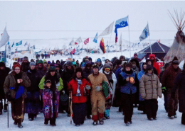 Beatrice Menase Kwe Jackson, center, and Daniel Emory, both of the Ojibwe Tribe, lead a procession to the Cannonball River in December as part of protests against the Dakota Access oil pipeline in Cannon Ball, N.D. (David Goldman / Associated Press)
