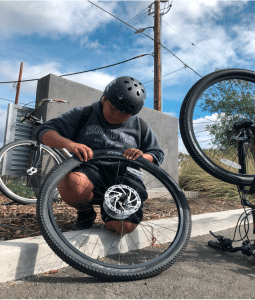 Arlene patching a punctured tube during a group ride to Southwest Community Park