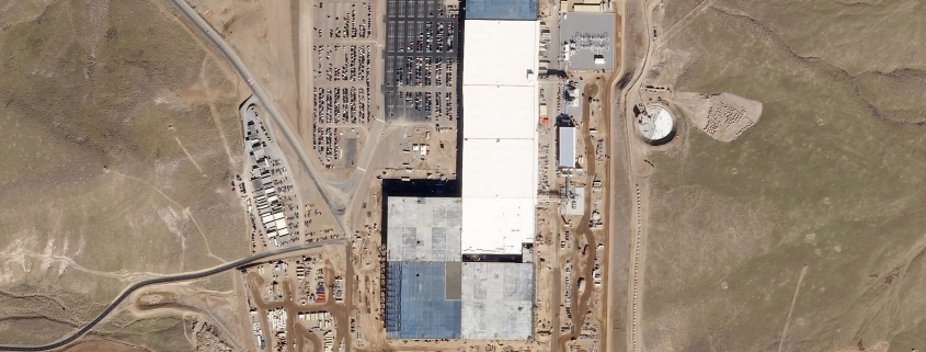 """Outside of Sparks, Nevada, construction of Tesla's """"Gigafactory"""" progresses over a 15-month period. The enormous plant now manufactures the unique battery packs that power Tesla's new Model 3 vehicle. Data analysis firms like Genscape use Planet imagery and other complementary datasets to analyze the health of the world's manufacturers."""