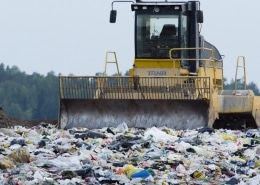 Tractor pushing garbage in a landfill.